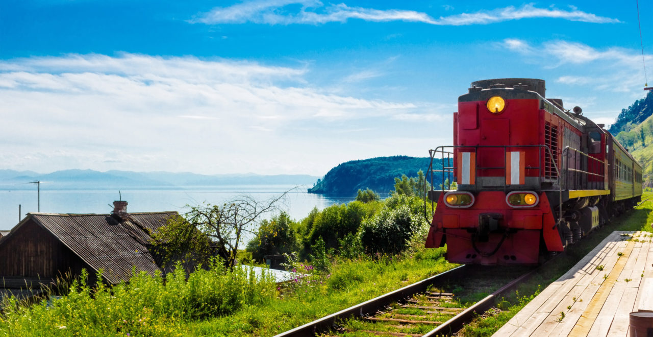 Landscape for travel with the arrival of a red train on a wooden deserted platform Circum-Baikal railway in a village on Lake Baikal in a bright summer sunny day.