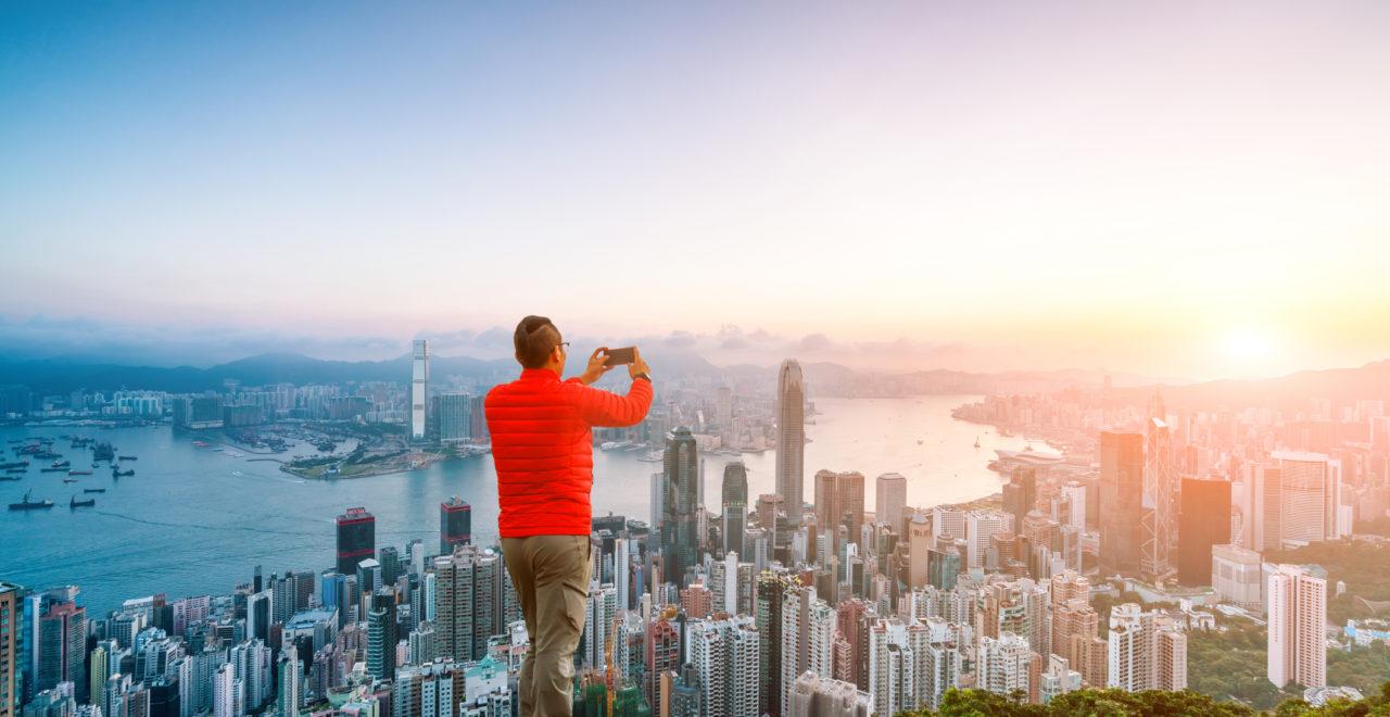man climbing to the rock facing Hong Kong skyline, Kina
